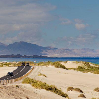 Road through the Corralejo Dunes, Fuerteventura, with Lanzarote in the background.